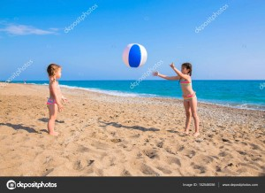 Children playing with beach ball outdoors.